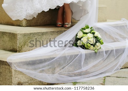 Wedding bouquet with Bride veil on the stairs in landscape orientated photo, focused to the Wedding bouquet - stock photo