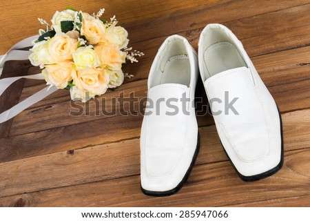 Wedding bouquet with groom's shoes on wood floor background - stock photo