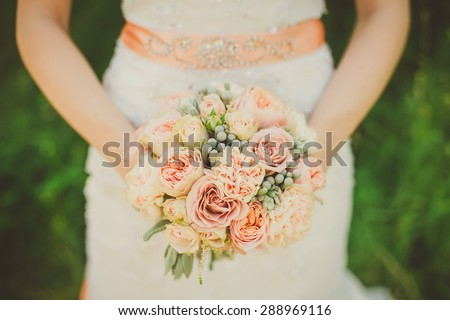 Wedding bouquet with peach and tender flowers in the hands of the bride - stock photo