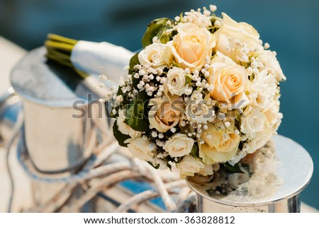Wedding bouquet with roses on the bollard in yacht club