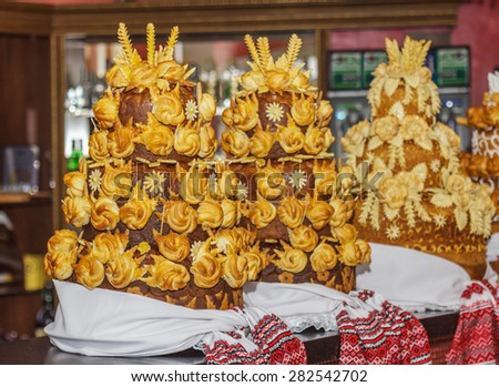 Wedding bread decorated with flowers - traditional Ukrainian round loaf an embroidery towel - stock photo