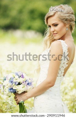 Wedding bridal bouquet in her delicate hands. Bride standing in a field
