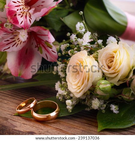 Wedding bridal bouquet of white roses and pink lilies with wedding rings on a wooden table, close-up - stock photo
