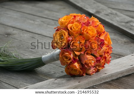 Wedding bridal bouquet with bright orange roses on old wood - stock photo