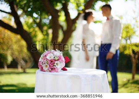 Wedding bridal bouquet with pink and white flowers on the table in the garden against the background of the bride and groom. Wedding concept - stock photo