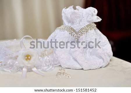 Wedding bride's handbag, necklace and earrings are on the table - stock photo
