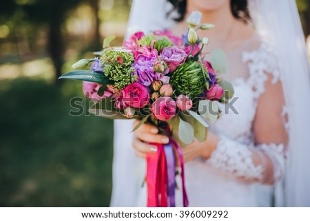 Wedding. Bride. The bride's bouquet. Bridal bouquet. The bride in a white dress holding a bunch of red, pink, blue flowers on background of green field