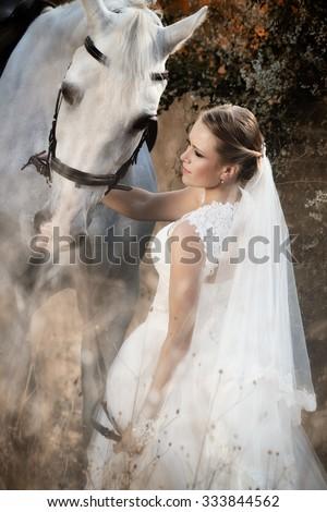 Wedding. Bride with white horse in autumn - stock photo