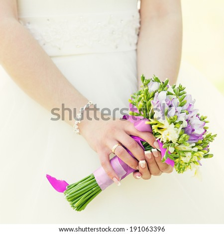 Wedding bunch of flowers in hands of the bride