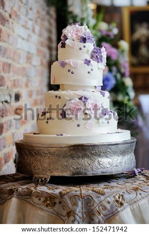 Wedding cake at reception with pink and purple flower decoration