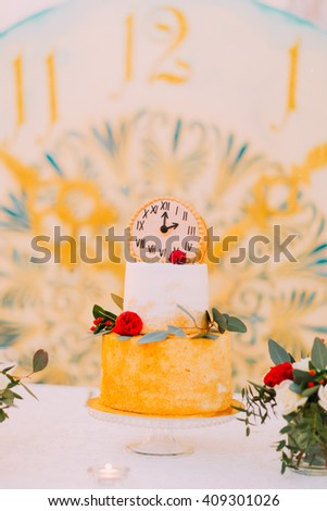 Wedding cake decorated with clocks and flowers close up