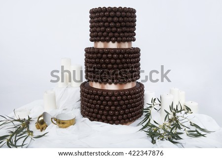 Wedding cake decorated with  greens costs on a white table decorated greece style with white  walls and gold cups. Delicious  chocolate wedding cake with sweet candy. olive branch - stock photo