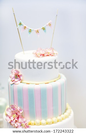 Wedding cake decorated with pink rose flowers and pearls - stock photo