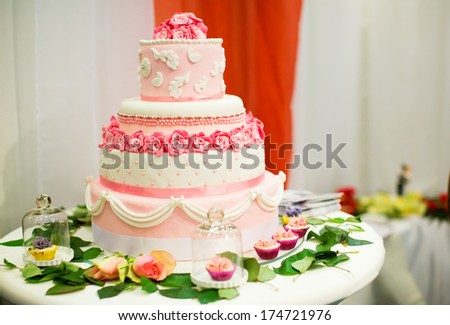 Wedding cake decorated with pink roses - stock photo