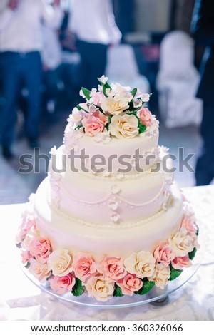wedding cake decorated with roses - stock photo