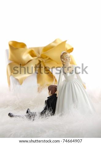 Wedding cake figures with gold ribbon gift on white - stock photo