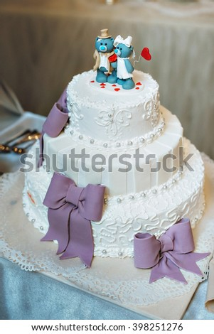 Wedding cake in lilac purple color. With decorative bows, figurines blue bears on the cake.