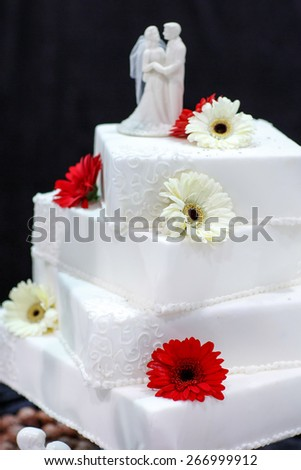 Wedding cake in white decorated with flowers and bride and groom figures - stock photo