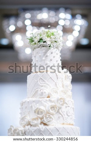 Wedding Cake Isolated in wedding party room, a multi level white wedding cake and  flowers on top - stock photo