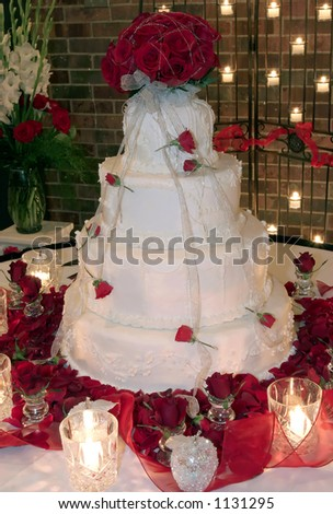 Wedding cake surrounded by rose petals and candles. - stock photo
