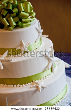 wedding cake with a green bow and an ocean theme - stock photo