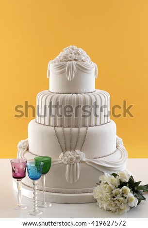 wedding cake with colored glass behind orange wallpaper - stock photo