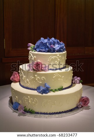 Wedding cake with flowers on reception table with dramatic lighting - stock photo