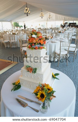 Wedding cake with flowers on table at reception - stock photo