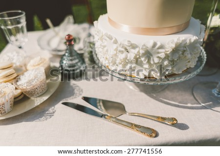 wedding cake with fondant cakes and macaroons on the table knife fork spatula and decor - stock photo
