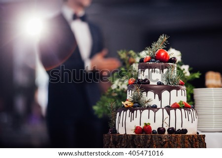 Wedding cake with fruits and chocolate on wooden substrate - stock photo