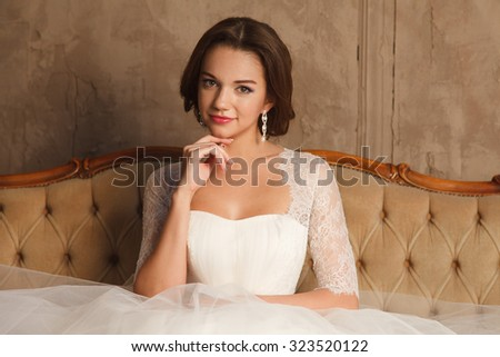Wedding Celebration. Beautiful young bride in white wedding dress. Indoor studio with beautiful furniture. - stock photo