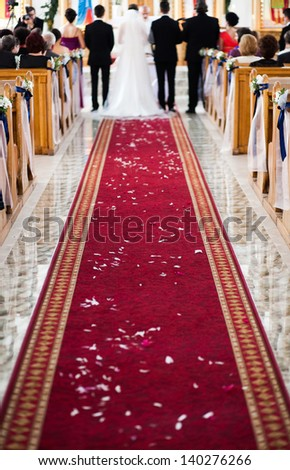 Wedding ceremony in church - focus on red carpet - stock photo