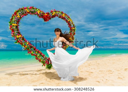 Wedding ceremony on a tropical beach. Happy bride under the wedding arch in the form of heart decorated with flowers on tropical sand beach. Wedding and honeymoon concept. - stock photo