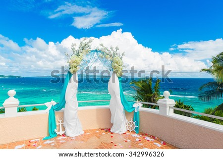 Wedding ceremony on a tropical beach in blue. Arch decorated with flowers on hotel, tropical sea in the background. Wedding and honeymoon concept. - stock photo