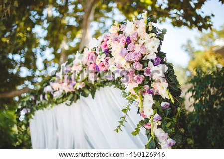 Wedding ceremony outdoors. Wedding arch in white with fresh flowers.