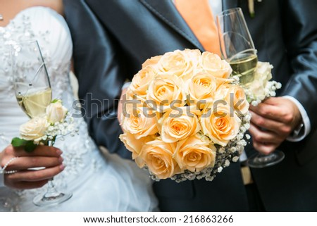 Wedding champagne glasses in hands of bride and groom - stock photo