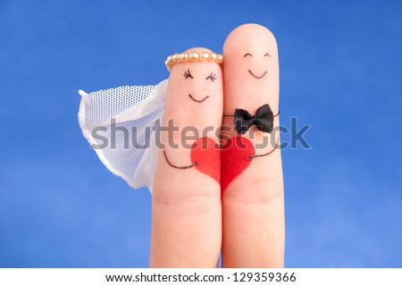 wedding concept -  newlyweds painted at fingers against blue sky, good use for wedding invitation card - stock photo