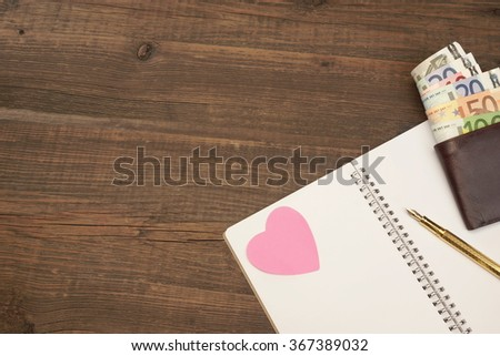 Wedding Costs Concept Image. Hearts, Gold Pen, Notepad With Blank Paper, Male Wallet With Dollar Cash On The Wood Background With Copy Space, Top View - stock photo