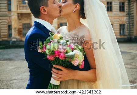 wedding couple. Beautiful bride and groom. Just married. Close up. wedding kiss. Groom kissing bride near castle - stock photo