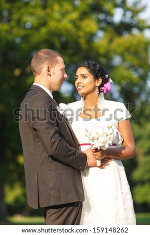 Wedding couple: Beautiful indian bride and caucasian groom in summer park - stock photo