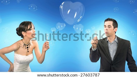Wedding couple blowing heart shaped romantic soap bubbles - stock photo