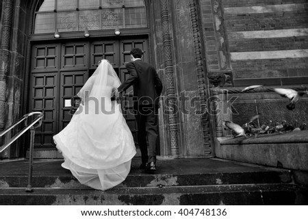 Wedding couple, bride and groom going for registration in Radhus Town Hall of Copenhagen, steps occupied by pigeons  - stock photo
