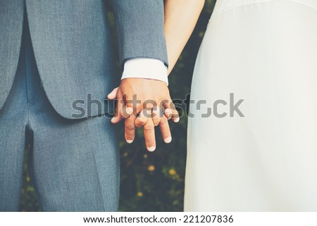 Wedding Couple, Bride and Groom Holding Hands - stock photo
