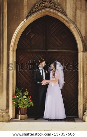 wedding couple, bride and groom stands against church - stock photo
