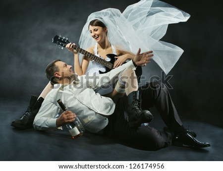 Wedding couple celebrating, singing, drinking and playing guitar. Bride in rock style. - stock photo