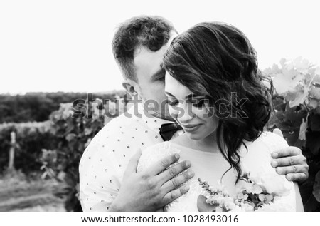 wedding couple - happy bride and groom embrace in vineyards, beautiful spring landscape, black and white photo