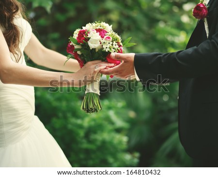 Wedding couple holding hands, groom and bride together on wedding day. - stock photo