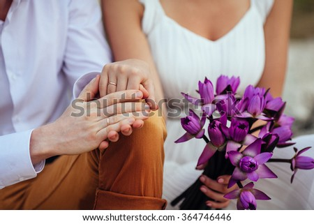 Wedding couple holding hands on beach with tropical bouquet