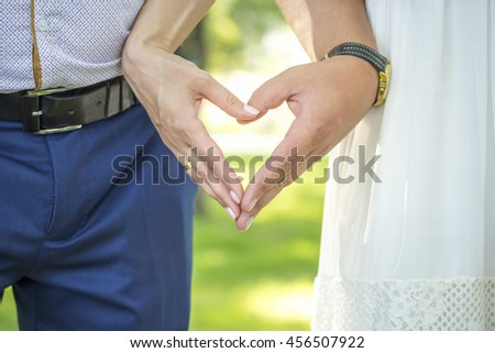 Wedding couple holding hands on nature background. Hands in the shape of heart.