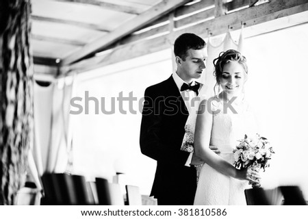 Wedding couple hugging at wooden  cafe